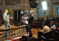 The camera is rolling as 'Chuck' explains the symbolism of the Advent wreath.