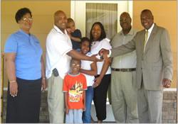 A happy family receives the keys to their new home from Rust College President David L. Beckley.