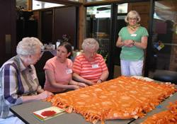 Making blankets for a shelter for homeless women and children was among the activities when several generations gathered for a Women's Retreat sponsored by First United Methodist Church in Des Moines, Iowa.