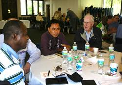 Bishop Rodolfo Juan (center) and retired Blshop Robert Spain (right) visit during a recent meeting of the United Methodist Council of Bishops.