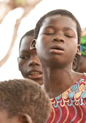 A child sings and prays at Kholosi United Methodist Church, part of the Ngabu Circuit in Malawi.