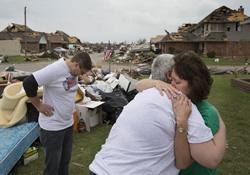 Homeowner Connie Boevers (right) is comforted by the Rev. Tish Malloy after a tornado swept through Boevers' neighborhood in Oklahoma City. At left is the Rev. Adam Shahan. Malloy is pastor of First United Methodist Church in Moore, Okla.