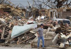 A man picks his way among tornado debris in Oklahoma City.