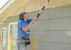 NOMAD Edie Mahan paints the exterior of the parsonage for El Mesias United Methodist Church in Alice, Texas.
