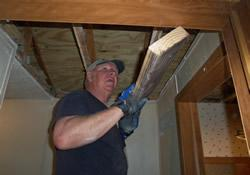 Wayne Mahan installs insulation prior to putting a new ceiling in a mobile home sponsored Community of Hope, an outreach of Caswell Springs United Methodist Church in Moss Springs, Miss.