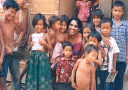 Missionary Clara Mridula Biswas gathers with some of the poor children with whom she serves in the slums of Phnom Penh, Cambodia. She assists children at an orphanage center with education, offers Christmas and Easter programs and religious education, and works with families who pick through garbage dumps to earn a meager living.
