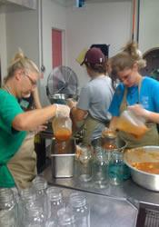Mission Service Team members can vegetable soup in the industrial cannery operated the Upper Sand Mountain Parish. Sales of the soup and green tomato products help support the parish's ministries.