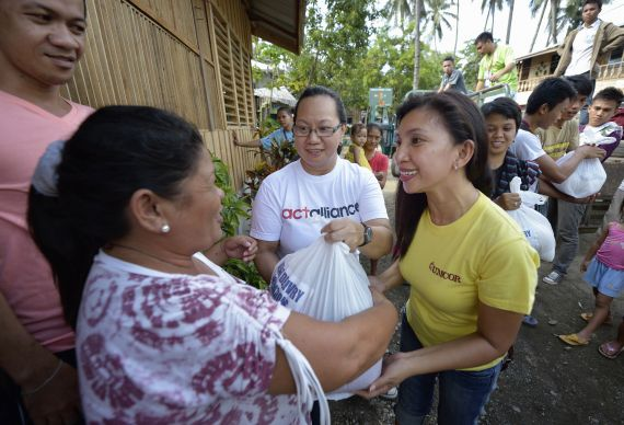 After the passage of Typhoon Bopha, Ciony Ayo-Eduarte (in yellow shirt), the director of operations in the Philippines for the United Methodist Committee on Relief, distributes emergency food supplies to people displaced by the storm in Iligan, on the southern Philippines island of Mindanao. Assisting her is Minnie Anne Calub (center), the emergency coordinator for the National Council of Churches of the Philippines.