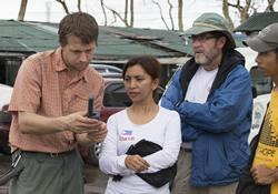 Andris Bjornson from Inveneo (left) demonstrates the use of a satellite phone for (from left) Ciony Ayo-Eduarte, manager for UMCOR in the Philippines; the Rev. Jack Amick, UMCOR head of international disaster response for UMCOR; and Ernani Celzo, working with United Methodist Communications following Typhoon Haiyan in Tacloban, Philippines.