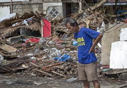 A member of a search team pauses amid the rubble left by Typhoon Haiyan.