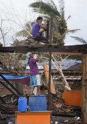 Freddie Santos (top) and Angelo Catanga work to erect a temporary roof for a friend whose home was laid open to the sky by Typhoon Haiyan in Tacloban, Philippines.