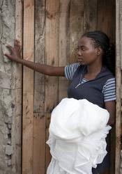 A woman prepares to hang the new insecticide bed nets she received during a distribution as part of the Imagine No Malaria campaign in Bom Jesus, Angola.