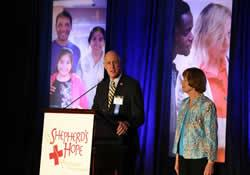 The Rev. Bill Barnes addresses a fund-raising event to benefit Shepherd's Hope, a multi-site medical clinic begun 17 years ago by St. Luke's United Methodist Church, Orlando, Fla. With him is Ruth McKeefery, the first volunteer president of Shepherd's Hope.