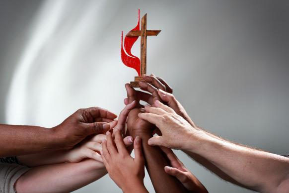 Different hands hold up the Cross and Flame of The United Methodist Church. Photo illustration by Kathleen Barry, United Methodist Communications.