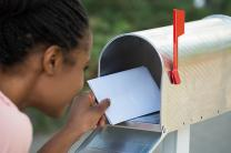 Woman taking letters out of a mailbox. Image by Andrey Popov, iStockphoto.com.
