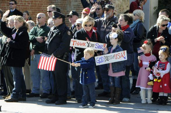An American boy waves a flag during a Veterans Day parade in Knoxville, Tenn., Nov. 11, 2011.n Photo from DefenseImagery.mil, courtesy of Wikimedia Commons.
