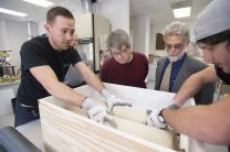 Nathan Porterfield (far left) and Carlos Perez (far right) of Unified Fine Arts in Dallas pack Bridwell Library's Chinese Torah scroll into a crate specifically built for transporting the scroll. Eric White (center left), Bridwell's Curator of Special Collections, and Daniel Slive, Bridwell's Head of Special Collections, look on.