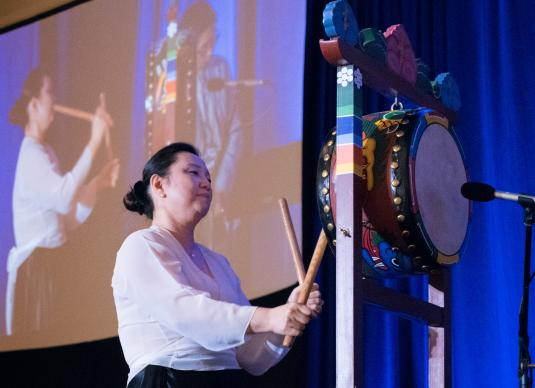 The Rev. Grace Pak, director of cross-racial/cross-cultural leadership for the United Methodist Commission on Religion and Race, plays a drum to call attendees of Facing the Future 2018 to worship. Photo by Joey Butler, UMNS.