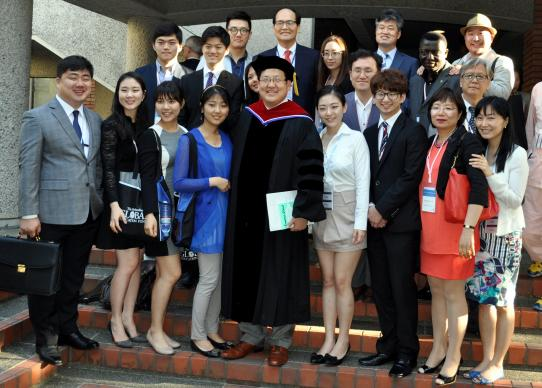 Young Min Paik with the APAEMI (Asia Pacific Association of Methodist-related Educational Institutions) delegation is surrounded by others at the 2014 International Association of Methodist Schools, Colleges and Universities held in Hiroshima, Japan. Photo by Kimberly Lord, General Board of Higher Education and Ministry.