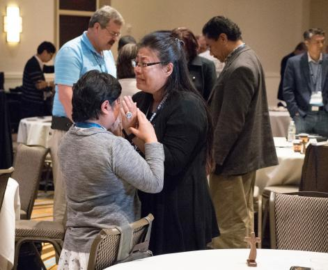 Two attendees weep while praying for one another at Facing the Future 2018. Photo by Joey Butler, UMNS.
