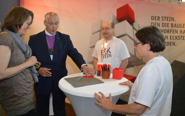 "Bishop B. Michael Watson, the Council of Bishop's ecumenical officer, demonstrates ""Re-formation"" with a wooden puzzel while visiting The United Methodist Church's booth at the German Kirchentag (German Church Day) in Berlin, Germany, in May. The puzzle will be used again at the church's booth at the World Reformation Exhibition in Wittenberg, Germany, July 11-17. Photo by Klaus Ulrich Ruof, Office of Communications, United Methodist Church Germany."