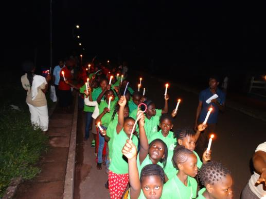 Children lead a candlelight procession into the Moyamba community before attending a social night at the Sierra Leone Conference's children's camp in late July.  Photo by Phileas Jusu, UMNS