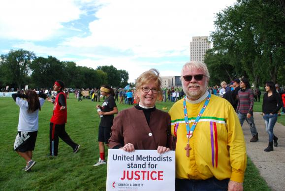 The Rev. Susan Henry-Crowe, general secretary for the United Methodist Church and Society and Fr. John Floberg, rector of Episcopal churches St James, St. Luke's and Church of the Cross on the Standing Rock nation, stand outside the North Dakota state capitol grounds in Bismark. Photo by John Hill, Church and Society