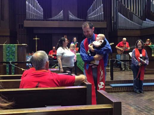 Lead pastor Scott Spencer introduces a child he has baptized to the congregation. Photo courtesy of Mosaic United Methodist Church