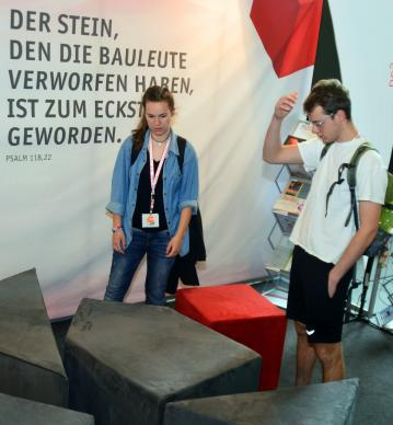 "Two young visitors struggle with a three-dimensional puzzle representing ""Re-formation"" at German Kirchentag (German Church Day) in Berlin, Germany, in May. The passage in German reads, ""The stone that the builders rejected has become the cornerstone."" Photo by Klaus Ulrich Ruof, Office of Communications, United Methodist Church Germany."