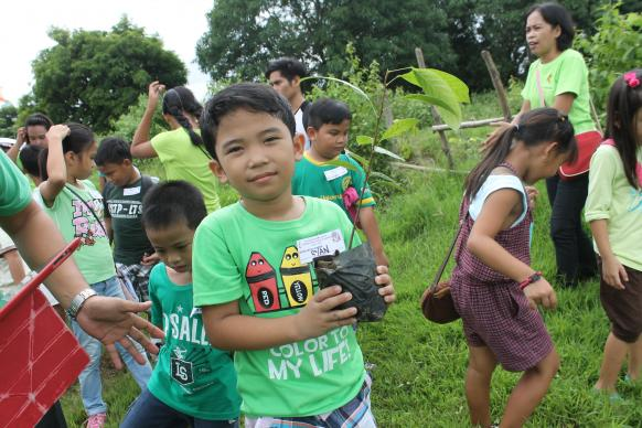 Ryan Dumaya holds up a seedling to be planted as part of The United Methodist Church's efforts to protect the environment in the Philippines. Photo by Gladys Mangiduyos, UMNS.
