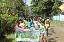 Sixty-two children march down a muddy road to join a tree planting in Macatbong, a barangay or village in Cabanatuan City. Photo by Gladys Mangiduyos, UMNS.