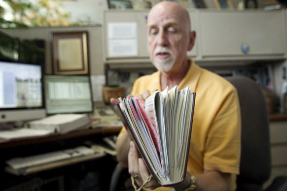 In this file photo, Marvin Cropsey leafs through his copy of the 2008 United Methodist Book of Discipline that contains pages of notations for corrections to be added to the 2012 version. Photo by Mike DuBose, UMNS.