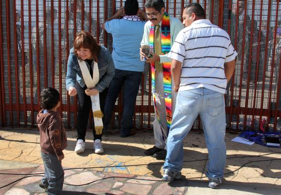 Bishop Minerva G. Carcaño shares communion bread with a little boy and his father in El Faro Park at the U.S./Mexico border. To her right is Pastor Felipe Ruiz Aguilar. 2013 file photo by Kathleen Barry, UMNS.