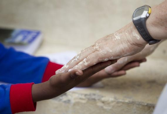 Her hands spattered with paint, volunteer Kathy Ahmad (right) plays a game with Franckenson Renevil during a break from renovating the Methodist Children's Home orphanage in Port-au-Prince, Haiti, in 2010. Photo by Mike DuBose, United Methodist News Service.