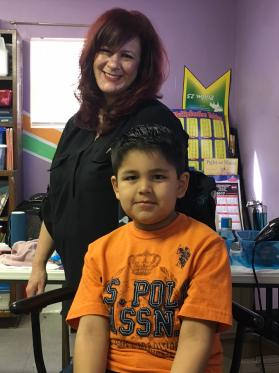 Native American children receive free back-to-school haircuts from Nikki Humbles, a licensed cosmetologist from Brock, Texas, on Jan. 27, 2018, at Clinton Church and Community Center. Humbles says she finds great joy in working with the children and families and hopes to make this an annual event. Photo courtesy of Clinton Church and Community Center.