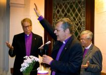 Bishop Frank de Nully Brown, who leads the Evangelical Methodist Church of Argentina, raises his handing in blessing during the dedication of the United Methodist Global Ministries and Upper Room regional office in Bueno Aires, Argentina. In the background (from left) are Florida Bishop Ken Carter and Bishop Stanley S. Moraes of the Methodist Church of Brazil. Photo by Gustavo Vasquez, UMNS
