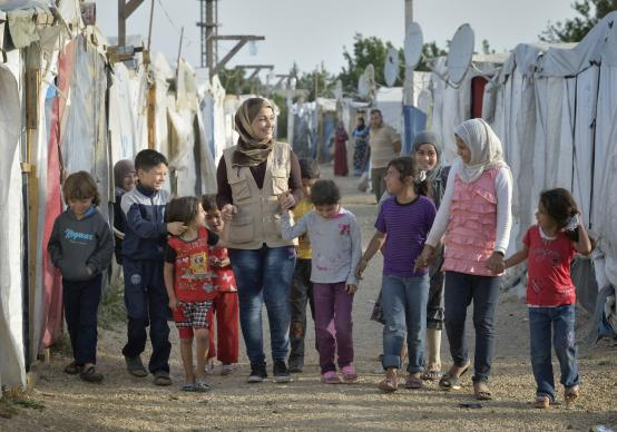 Ahlam Al Khaled, a health and nutrition educator for International Orthodox Christian Charities, walks with children in a settlement of Syrian refugees in Minyara, a village in the Akkar district of northern Lebanon. Photo by Paul Jeffrey for ACT Alliance