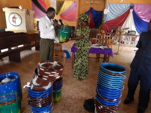 The Rev. Winston Ashcroft distributes hand-washing buckets to Rev Mariama Bockarie for the Makeni District.