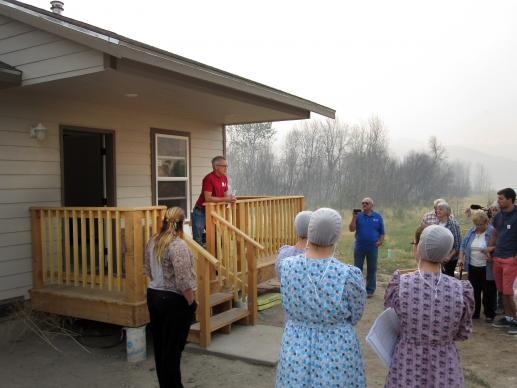 Kevin Froese, on deck at left, of Mennonite Disaster Service, speaks during the Aug. 23 dedication of the first of 11 houses to be completed by ecumenical volunteers after last year's Carlton Complex Fire in Washington. The house was framed by the Amish from Montana, the MDS and United Methodists finished the interior. Photo by Jim Truitt