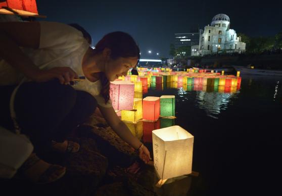 A woman sets a floating candle lantern on the river the 70th anniversary of the atomic bombing in Hiroshima, Japan. The Hiroshima Peace Memorial is in the background. Photo by Paul Jeffrey, World Council of Churches