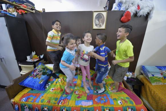 Iraqi children bounce on a bed in the basement of Sacred Heart Catholic Church in Amman, Jordan, where 60 Iraqi Christian refugees are living. Lutheran World Relief has helped the church feed the refugees and remodel the basement to provide some privacy for the 10 families. Photo by Paul Jeffrey for ACT Alliance