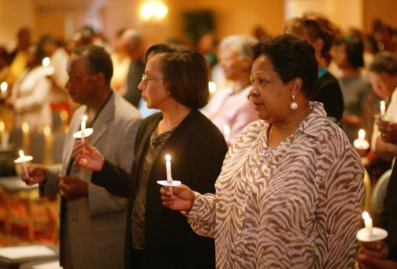 Participants at a 2004 reunion of the former Central Jurisdiction of the Methodist Church light candles in memory of those from the jurisdiction who have gone before them. The jurisdiction was a racially segregated structure for black Methodists that existed from 1939 to 1968. From left are: Earl Cleveland, Patricia White and Katie Harrison.