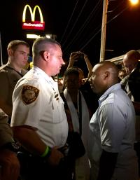 The Rev. F. Willis Johnson Jr., talks with a St. Louis County police officer about a United Methodist march in Ferguson, Mo. Photo by Kelley Hartnett