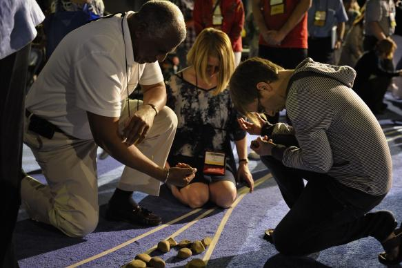 Delegates pick up stones in the center aisle during an April 27