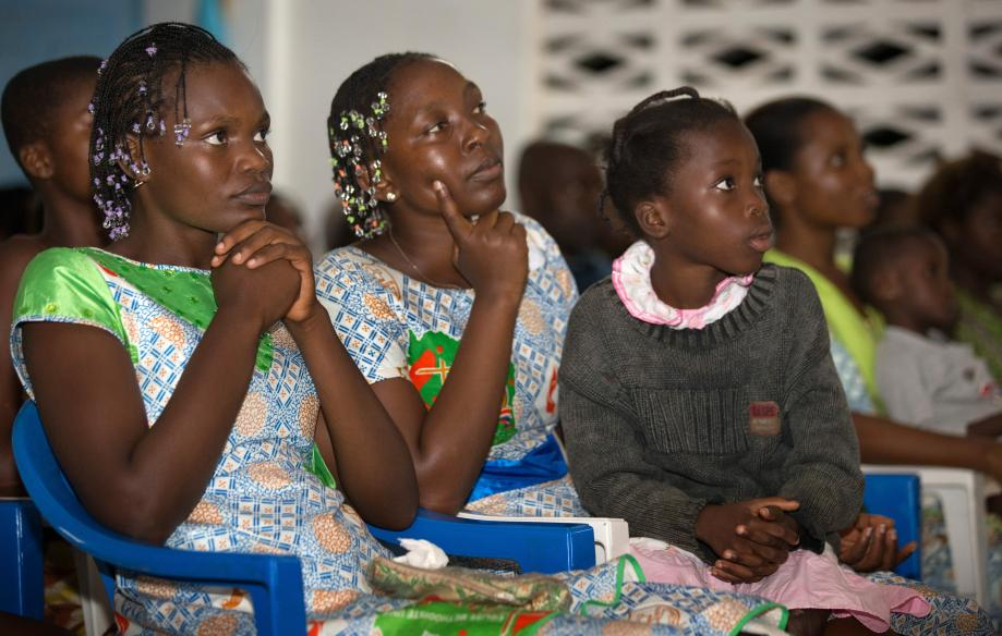 Young people listen to a presentation about preventing the spread of Ebola prepared by United Methodist Communications during a service at the United Methodist Church in Sassandra. From left are: Anaya Grace Camara, 22; Flore Diobo, 30; and Marie Yao, 9.