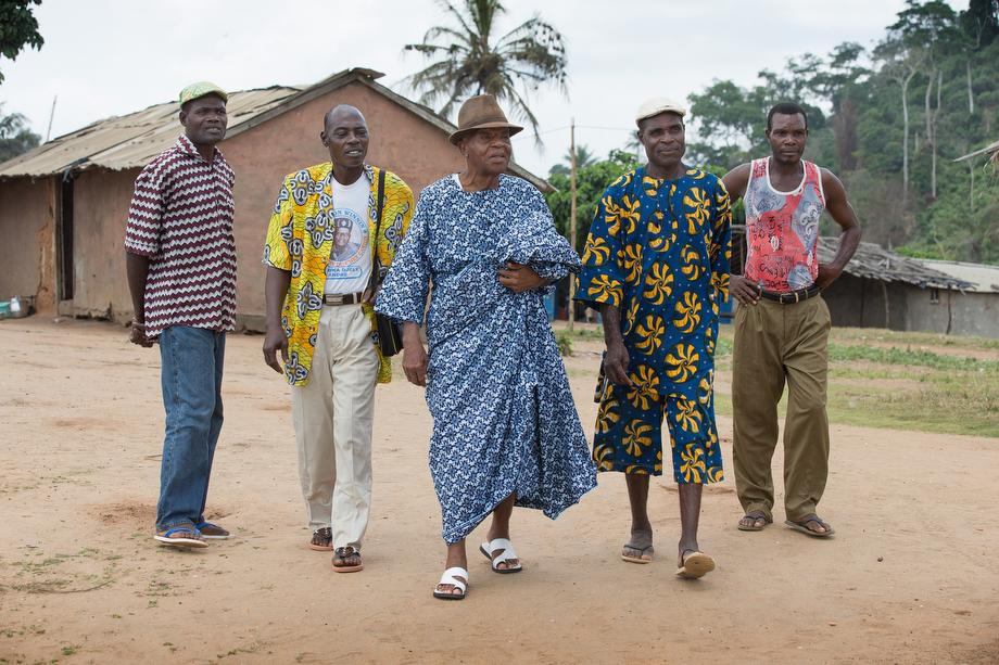 Chief André Djirika Djeli (center) and village elders walk through the fishing community of Monogaga.