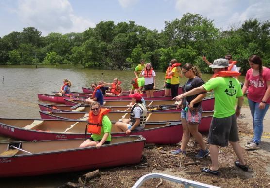 Rounding up enough canoes was one challenge in floating about 100 campers and staff to Cross Point United Methodist Camp in Kingston, Okla., on Monday, June 22. The camp is cut off from road access by recent floods. Photo courtesy Cross Point