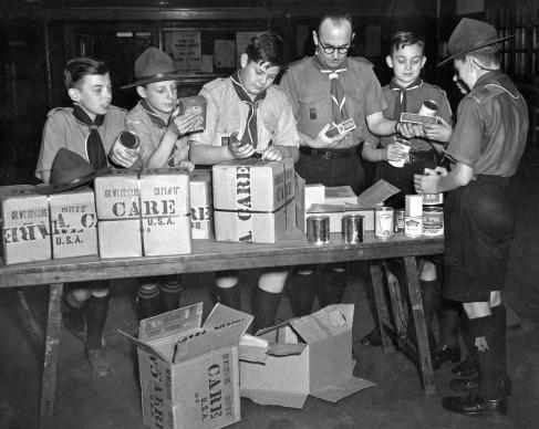 In 1948, U.S. Boy Scouts in Chicago sent five parcels of food through CARE to Boy Scouts in England. Pictured are J.M. Andrew, Scoutmaster and members of the Paddington Troop unpacking the parcels. After World War II, CARE distributed packages with food and other items to Europeans in need. Photo courtesy of CARE