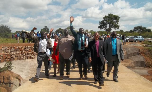 Bishop Eben K. Nhiwatiwa leads the congregation across the new Chitora-Gwarada Bridge. Raising his hand in the center is the Rev. Lloyd Nyarota. In the blue clerical shirt is the Rev. Daniel Chitsiku, Mutare district superintendent. Photo by Taurai Emmanuel Maforo