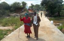 Taurai Emmanuel Maforo assists Keresia Muzaruwetu in crossing the new Chitora-Gwarada Bridge in Zimbabwe. Photo courtesy of Zimbabwe East Conference.